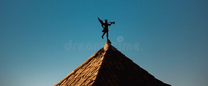 以吹小号天使的形式风向在屋顶 库存图片