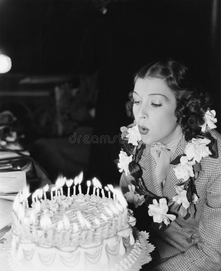 吹散在生日蛋糕的一个少妇的档案蜡烛(所有人被描述不更长生存,并且庄园不存在 免版税库存照片
