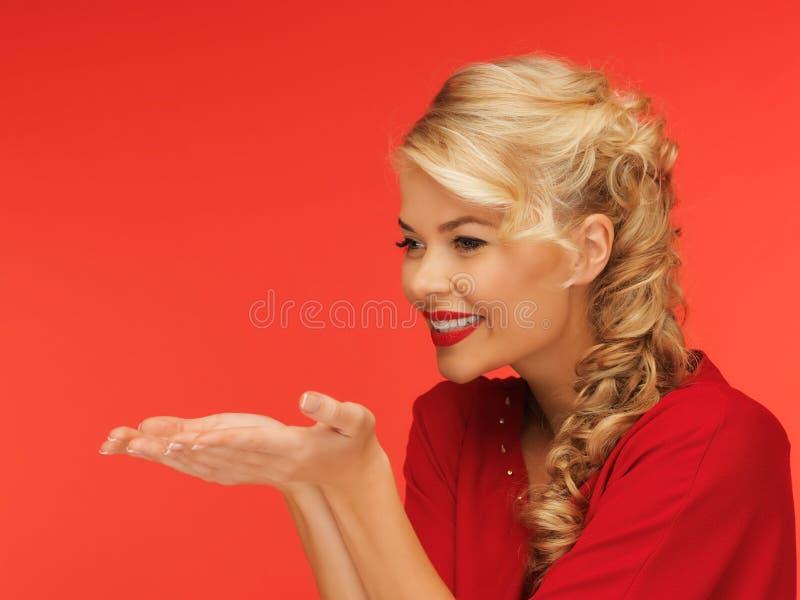 吹某事在她的手棕榈的妇女  免版税图库摄影