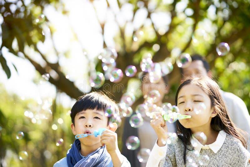 吹泡影的小亚裔孩子户外 免版税库存图片