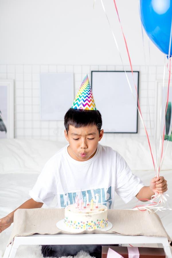 吹灭从蛋糕的亚裔帅哥蜡烛 图库摄影