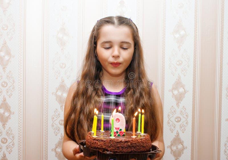 吹灭在蛋糕的小女孩蜡烛 免版税库存照片