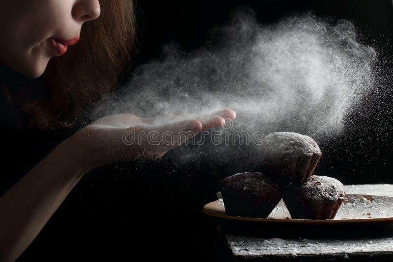 吹的搽粉的糖用在松饼的手 库存照片