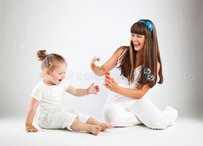 吹的泡影女孩她的小母亲 免版税图库摄影