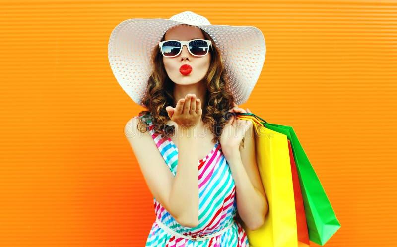 吹红色嘴唇的画象俏丽的妇女送与穿五颜六色的镶边礼服,夏天草帽的购物带来的甜空气亲吻 免版税库存图片