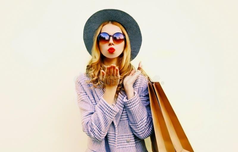 吹红色嘴唇的画象妇女送与购物带来的空气亲吻在桃红色外套,在墙壁上的圆的帽子 库存图片