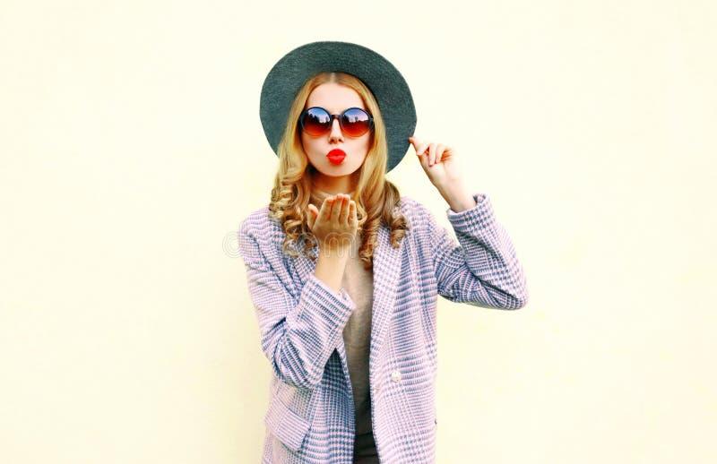 吹红色嘴唇的画象美丽的年轻女人送在圆的帽子的空气亲吻 免版税库存照片