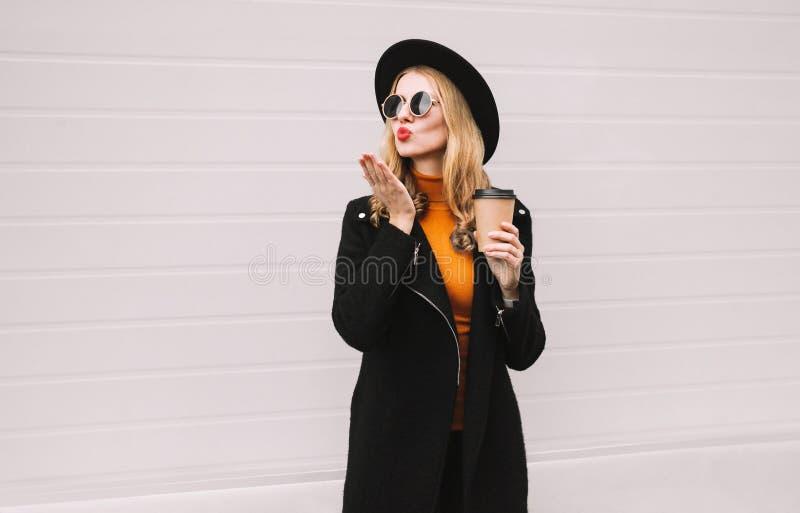 吹红色嘴唇的美女送与咖啡杯,佩带的黑色衣服,夹克外套,圆的帽子的甜空气亲吻 免版税库存图片