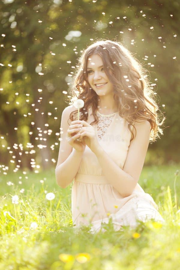 吹蒲公英的美丽的妇女 图库摄影