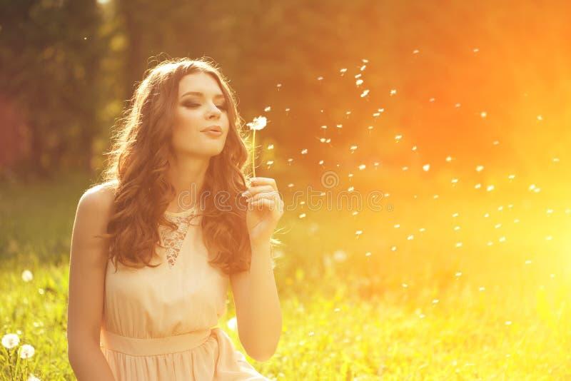 吹蒲公英的美丽的少妇 时髦女孩在 免版税库存图片