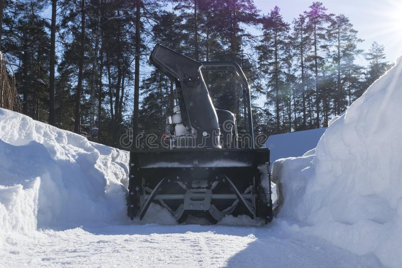 吹雪机在工作在一个冬日 取消雪的除雪机在飞雪以后 清除冰 积雪的清除机器 清楚的车道 库存图片