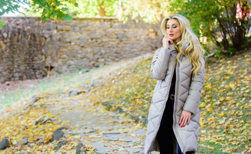 吹风者夹克偶然和舒适的样式 女孩时兴的白肤金发的步行在秋天公园 女服温暖的灰色夹克 库存照片
