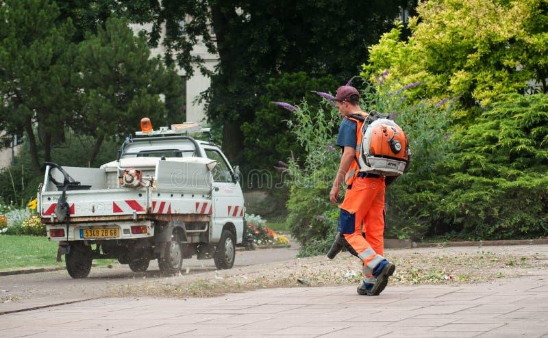 吹cutted草和死的叶子的花匠在都市公园 免版税图库摄影