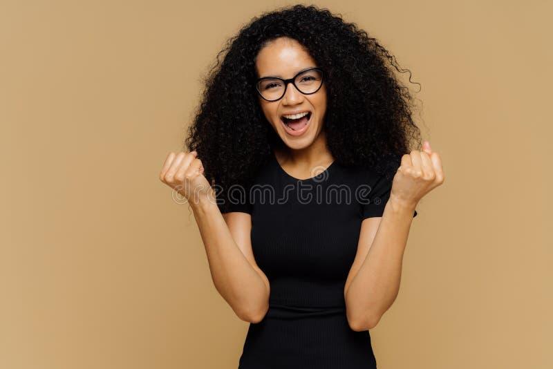 呀,我最后做了它!乐观可爱的深色皮肤的卷曲妇女举紧握拳头,从正面情感惊叹, 免版税库存照片
