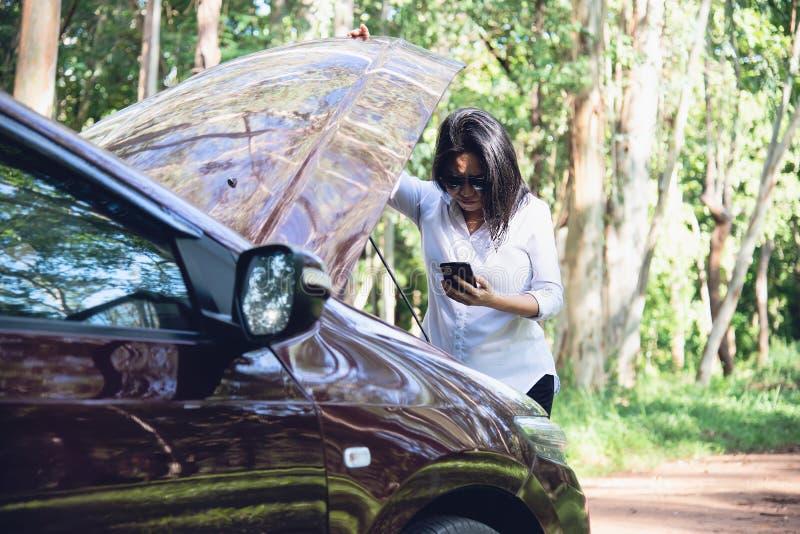 告诉亚裔的妇女安装工或保险职员解决在一条地方路的一个发动机问题 免版税库存图片