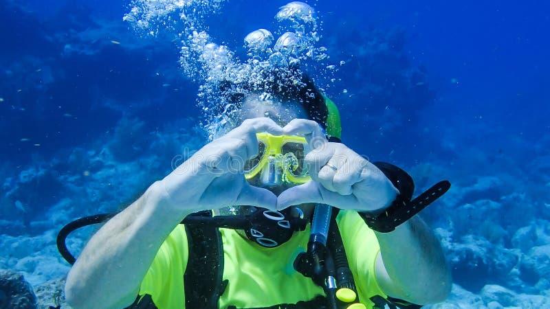 告诉佩戴水肺的潜水的丈夫他的妻子他爱她的水中 免版税库存照片