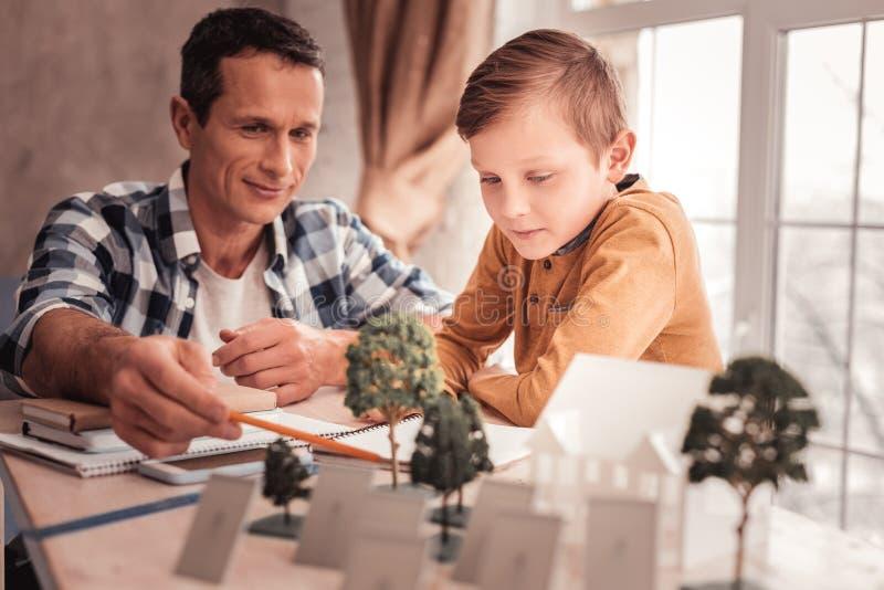 告诉关心的父亲他的关于dendrology的好奇金发的儿子 免版税库存图片