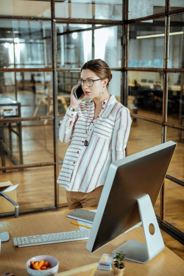 告诉怀孕的女实业家问她的医生有些问题 免版税库存图片