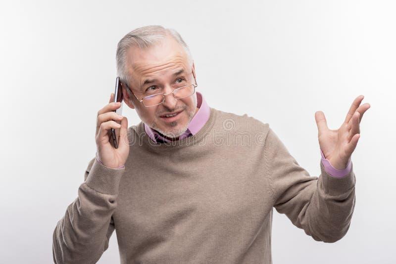告诉情感灰发的年迈的人他的商务伙伴 免版税库存照片