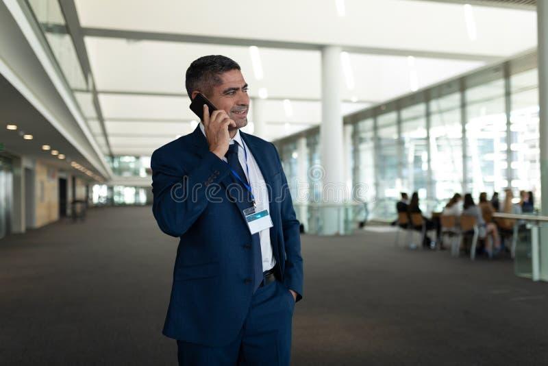 告诉某人手机的和看在办公室大厅的商人 库存图片