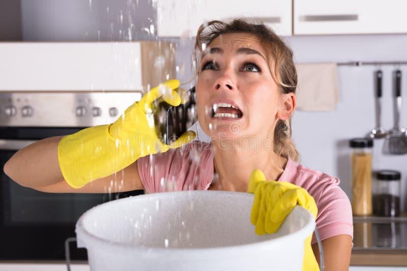 告诉的妇女水管工修理漏从天花板的水 免版税库存照片