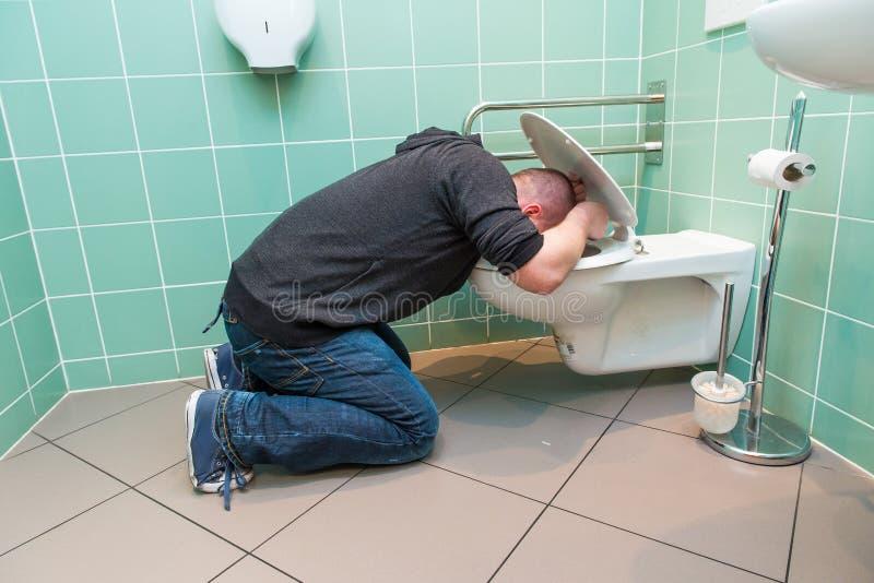 呕吐在洗手间的人 库存照片