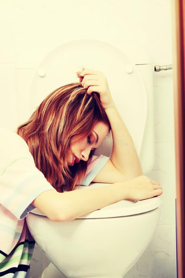 呕吐在洗手间的青少年的妇女 免版税库存照片