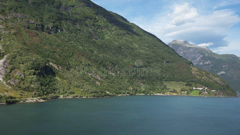 周围的峭壁的晴朗的看法和原始冰川海湾在ESCO被保护的盖朗厄尔峡湾,挪威浇灌 库存图片