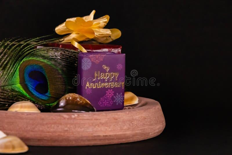 周年礼物概念 黑色背景上装饰礼盒、展贝的孔雀羽毛 免版税库存图片