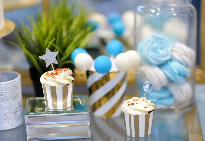 周年/婚姻的可口甜点心在蓝色和白色口气-杯形蛋糕,蛋白软糖,香草蛋糕流行音乐 时髦的甜点 免版税图库摄影