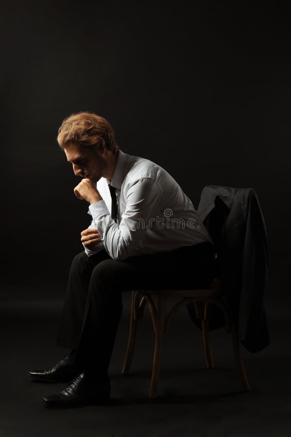 周道的商人坐椅子反对黑背景 图库摄影