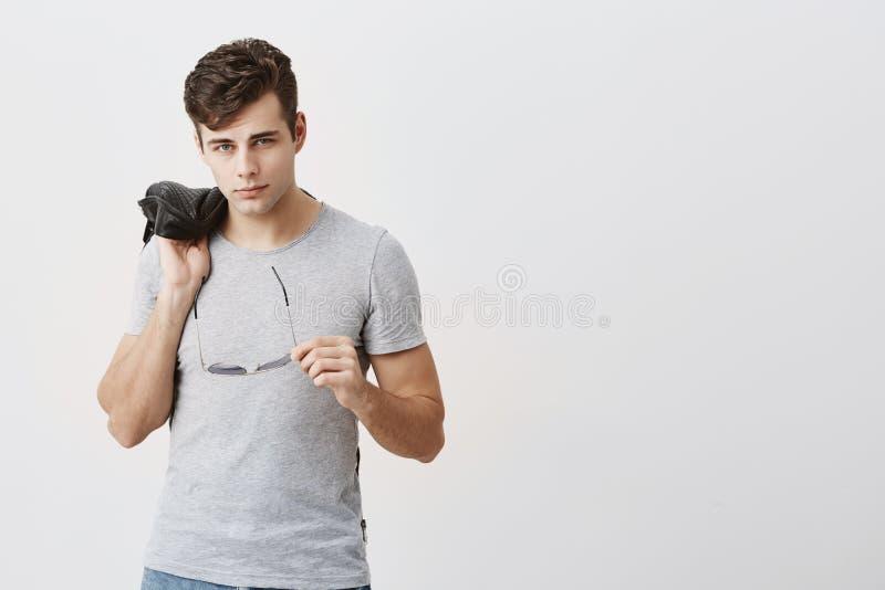 呼吁,摆在户内反对灰色背景的肌肉,确信的男性 有时髦理发的时髦的英俊的人 免版税库存图片