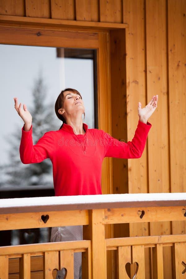 呼吸在她的阳台的妇女在冬天 免版税库存照片