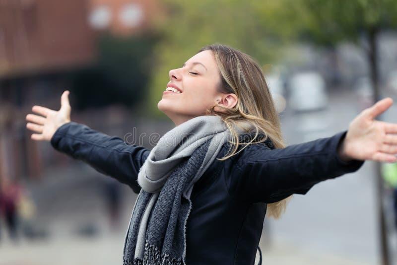 呼吸新鲜空气和举的微笑的年轻女人胳膊在城市 免版税库存照片