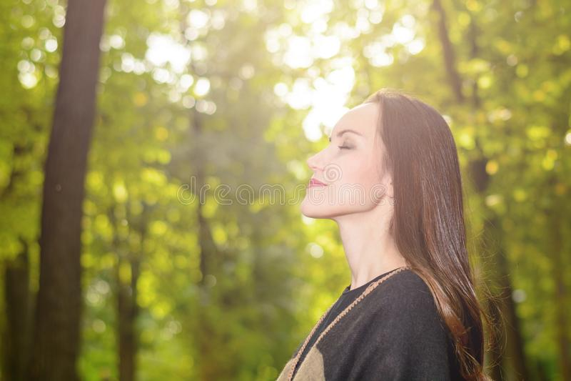 呼吸新鲜空气的妇女在一个绿色森林里在穿羊毛雨披的春天 免版税库存照片
