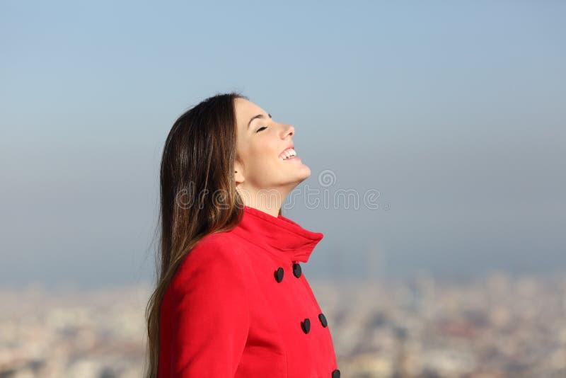 呼吸有都市背景的愉快的妇女在冬天 免版税库存照片
