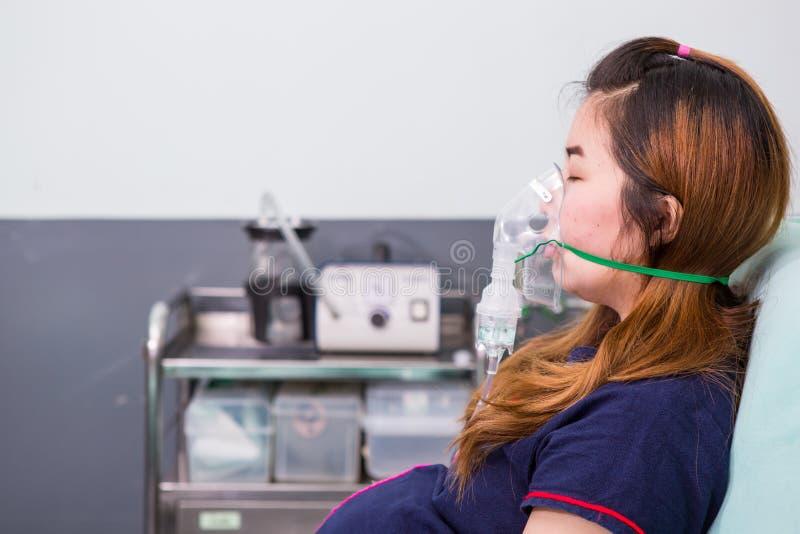 呼吸通过吸入器面具的妇女 免版税库存照片