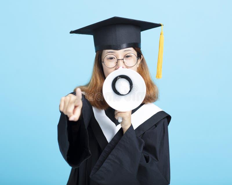 呼喊与扩音机的毕业生妇女 免版税库存图片