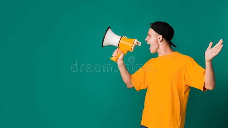 呼喊使用在绿松石背景的扩音机的少年 库存图片