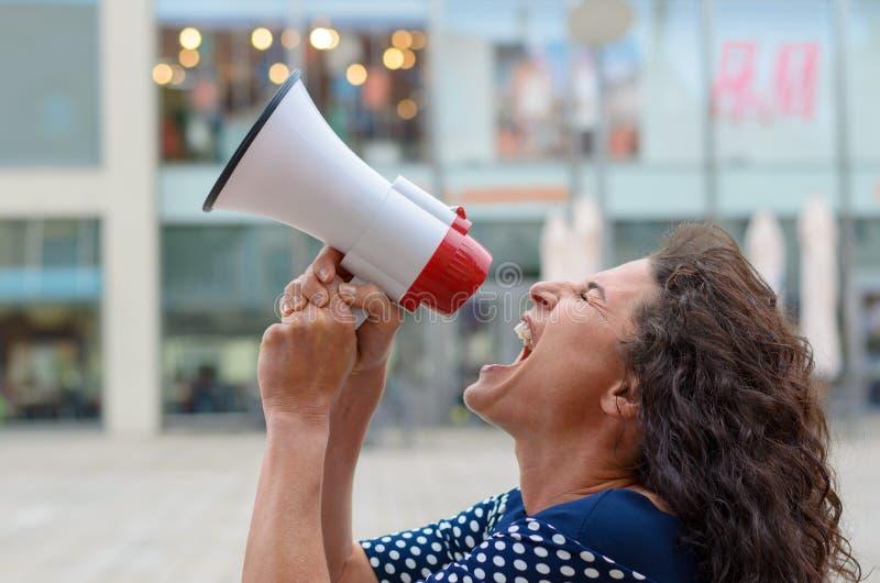 呼喊入扩音机的少妇抗议者 免版税图库摄影