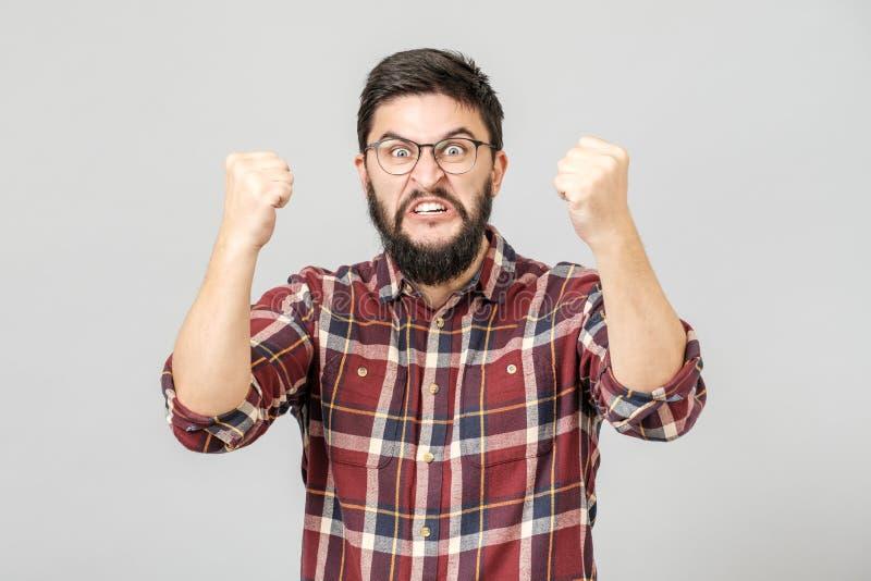 呼喊和握紧被举的拳头的英俊的有胡子的人画象,当胜利从成功时 免版税库存照片