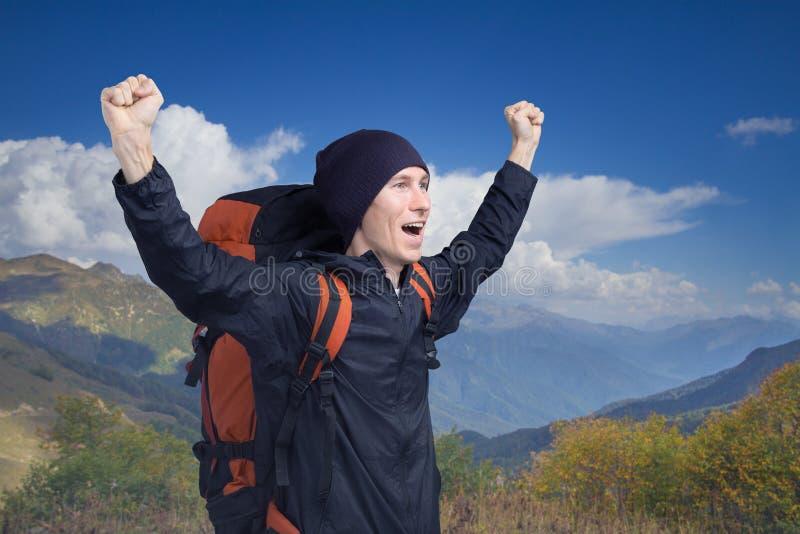 呼喊在上面的年轻徒步旅行者用他的手上升了,侧视图 免版税库存图片