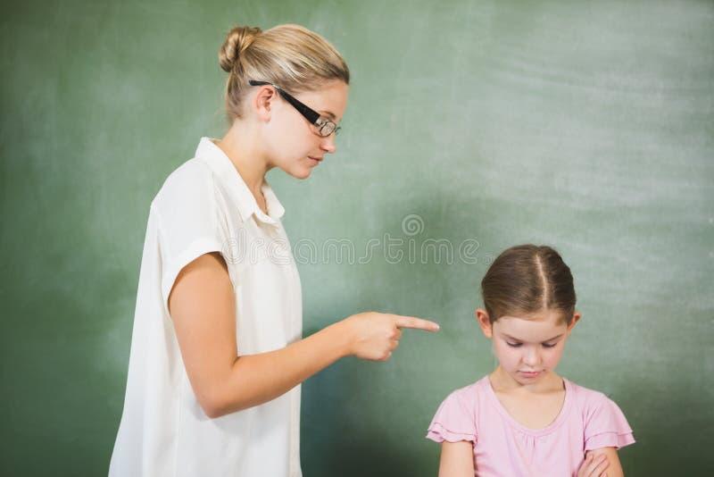 呼喊在女孩的女老师在教室 免版税图库摄影