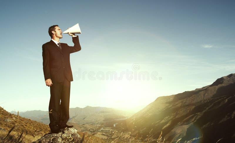 呼喊在山概念的上面的商人 免版税库存图片