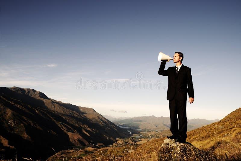 呼喊在山的上面的商人 图库摄影