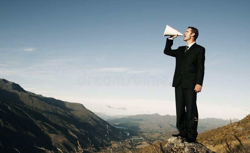 呼喊在山的上面的商人 库存照片
