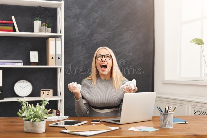 呼喊在工作地点的愤怒的女商人 图库摄影