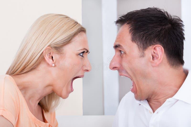 呼喊在彼此的恼怒的夫妇 免版税库存照片