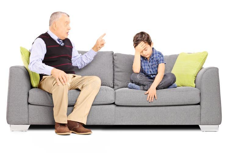 呼喊在他哀伤的侄子的恼怒的爷爷,安装在沙发 免版税库存照片
