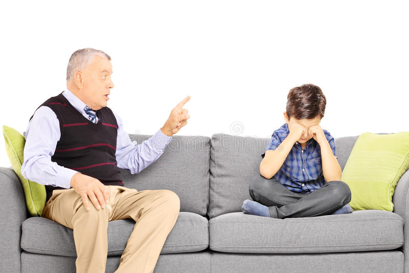 呼喊在他的侄子的恼怒的爷爷,安装在沙发 库存照片